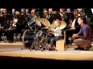 3-х летний мальчик играет на барабанах с оркестром