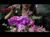 Professional woman florist makes the bouquet from pink flowers tulips, roses, orchids and solidago.
