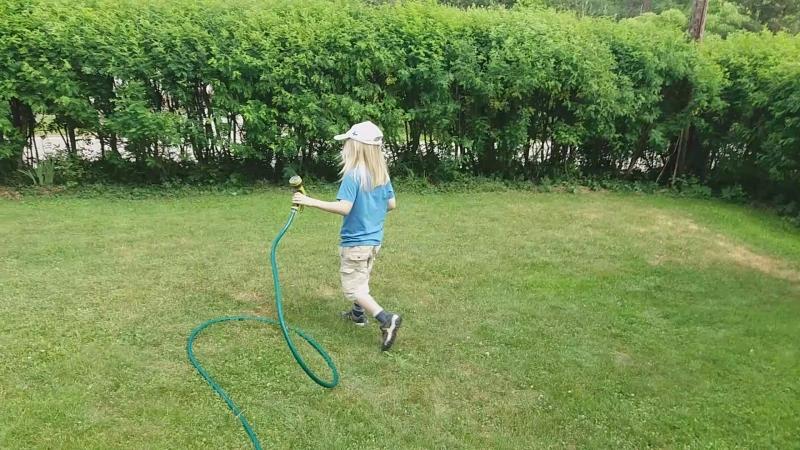 Тима поливает газон. На даче засуха.
