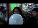 Women blow to pop large white balloons at party