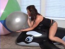Girl blow to pop a silver balloon