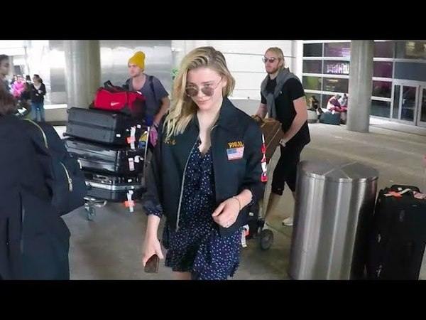 Chloe Moretz Smirks At Paparazzi Upon Arrival In L.A. From London