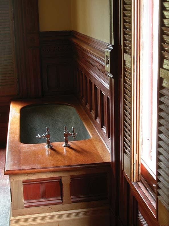 Эта восстановленная деревянная оцинкованная оловянная ванна с деревянной отделкой находится в Астории, в доме 1885 года в Флавеле в Орегоне.