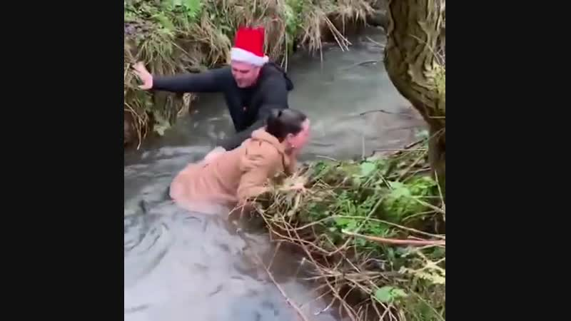 Woman tries to jump over stream but ends up dragging her boyfriend in too.