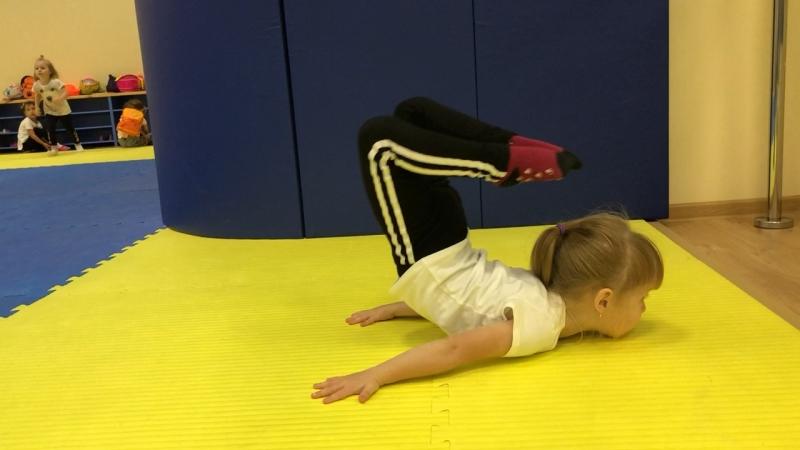 Стойка на груди для малышей с касанием ногами головы