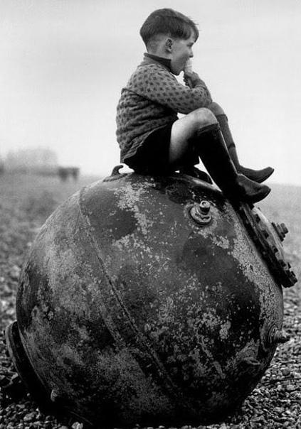 Фотография мальчика, который ест мороженое, сидя на морской мине. Англия.