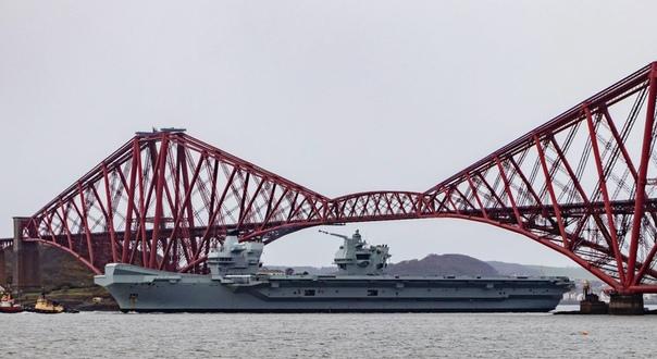 Новейший британский авианосец HMS Queen Elizabeth третьего апреля с г. проходит под железнодорожным мостом Forth Bridge, переброшенным через залив Ферт-оф-Форт на восточном берегу Шотландии.