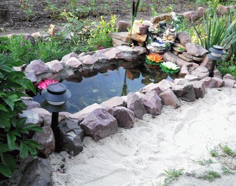 Пруд из старой ванны Вам потребуются: 1. Песок 50–70 кг. 2. Гравий для дренажа — 2 ведра. 3. Большая старая кастрюля без дна или лист жести 70х60 см. 4. Тачка, ведро, лопата. 5. Рулетка, измеритель уровня. 6. Длинная доска (по длине ванной). 1. Поставьте ванну на землю и с помощью колышков и натянутой между ними нити обозначьте границы будущего котлована. Добавьте еще 20 см для песчаной подушки. 2. Выройте яму, предварительно сняв слой дерна. Глубина должна быть такой, чтобы ванна оказалась…