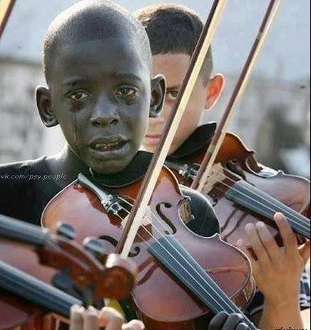 Ребенок играет на скрипке на похоронах своего учителя по музыке. Учитель спас его от нищеты и насилия.