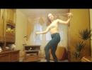 Девушка в йога-пэнтс танцует дома перед камерой.