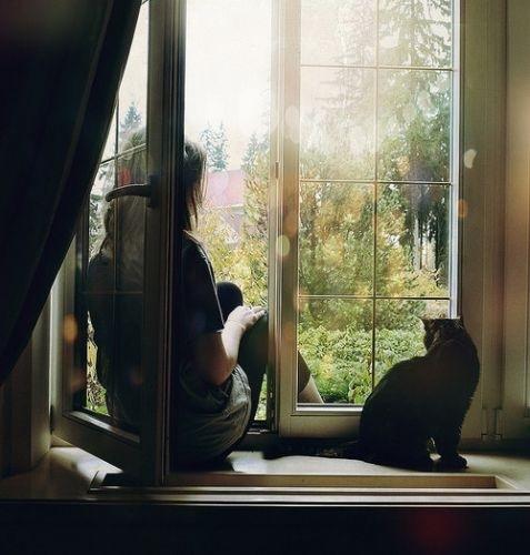 Фото Девушка сидит на подоконнике рядом с черной кошкой.