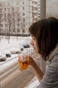 Девочка стоит на балконе в открытое окно и напитки горячий чай.