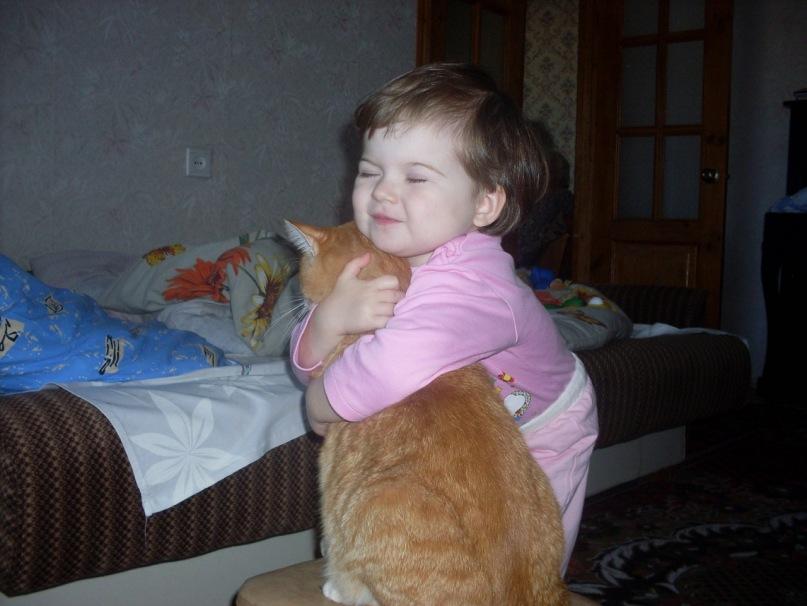 ребенок обнимает рыжего кота