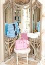 Розовая сумка и много коробочек возле большого старинного трюмо.