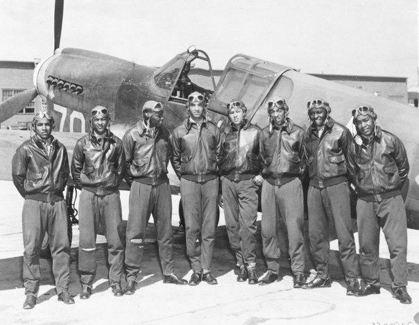 Чернокожие американские пилоты 99-й эскадрильи, более известной, как «Пилоты из Таскиги» на фоне самолета-истребителя P-40.