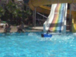 Карим катается с желтой горки в бассейне