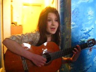 девушка очень красиво поет и играет на гитаре