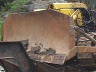 лесовоз везет на себе бульдозер по горной дороге