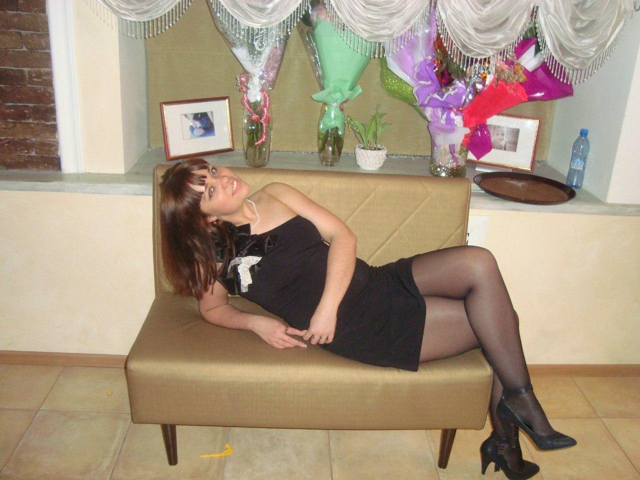 Девушка с белоснежной улыбкой полулежит на диване в длинном черном платье