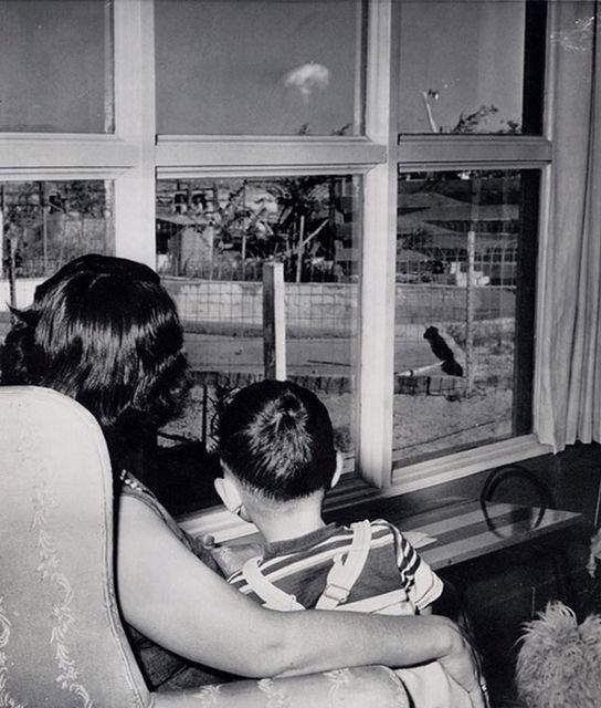 Мать и сын наблюдают за ядерным грибом, видным из их окна во время первых испытаний бомбы. 1953 год
