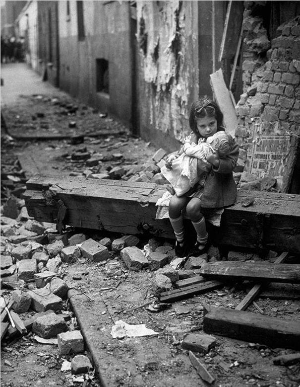 Маленькая девочка со своей куклой на руинах её дома в Лондоне. 1940 год