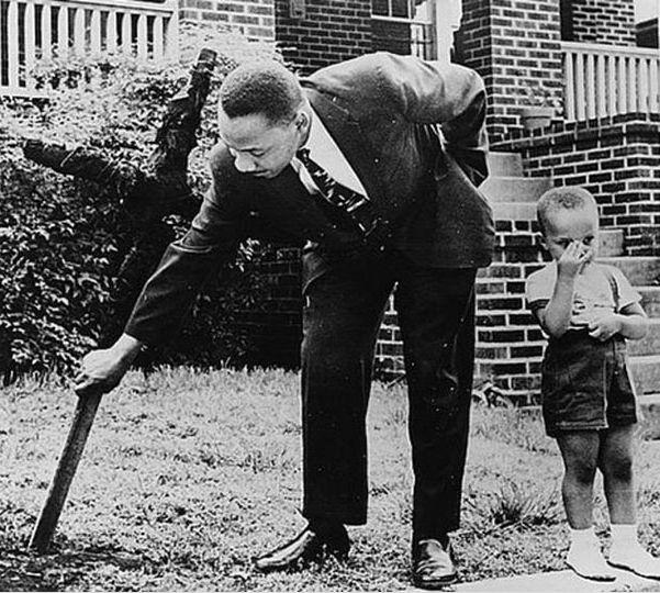 Мартин Лютер Кинг и его сын убирают сожженный крест со своего двора. 1960 год