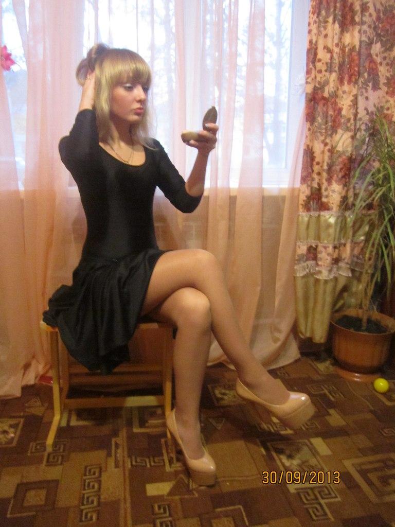 Девушка в черном платье в колготках