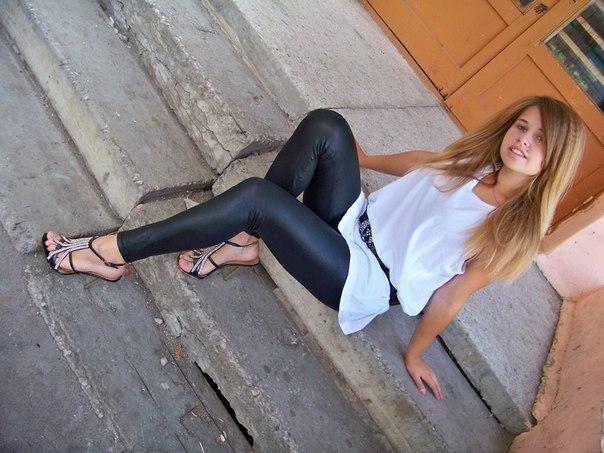 Блондиночка в белой длинной майке и черных леггинсах