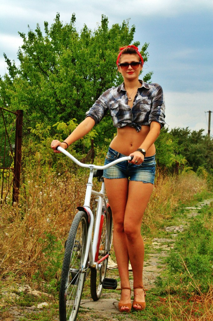 Девушка с велосипедом в клетчатой рубашке