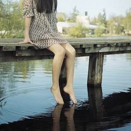 Дівчина опустила ноги на воду