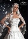 длинное, облегающее фигуру платье.  Стилисты советуют к такому наряду выбрать длинную фату-мантию...