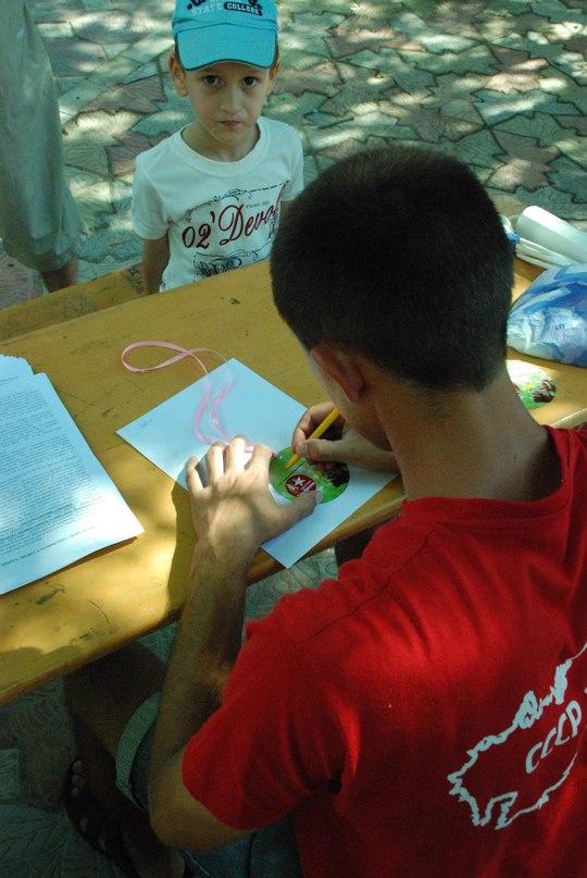 """Участник """"СВ-Севастополь"""" вручает юным участникам мероприятия именные бейджики"""
