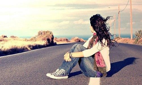 Дівчина на асфальті сидить в джинсах