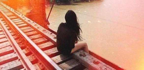 Дівчина сидить на колії і спустила голі ноги над водою