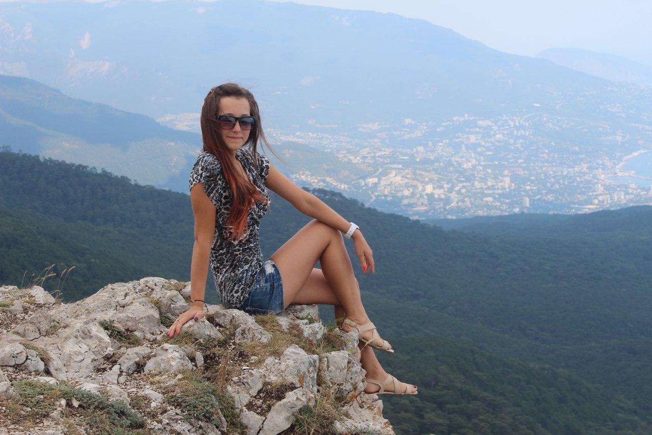 Девушка на вершине горы в пятнистой футболке
