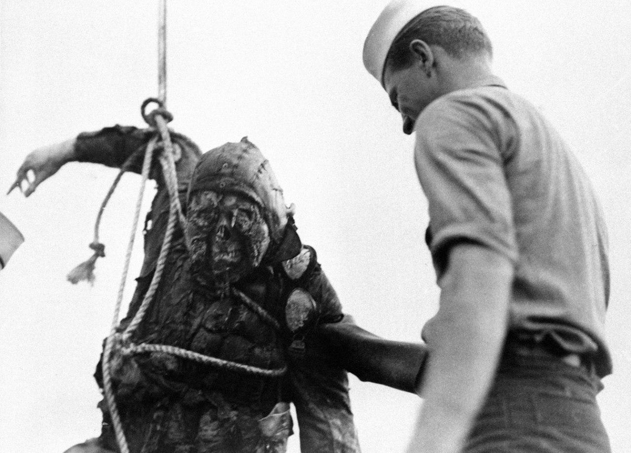 Американский матрос принимает участие в подъеме тела японского летчика, выловленного в бухте военно-морской базы Пёрл-Харбор после атаки японского авианосного соединения. Территория Гавайи. США. Декабрь 1941 года.