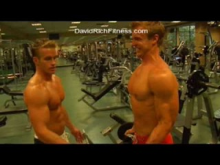 Male Fitness Models James Ellis and David Rich do an advanced dumbbell biceps exercise