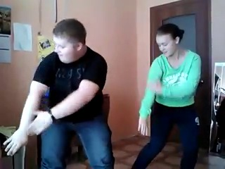 толстый парень с девушкой в офисе танцует на перерыве