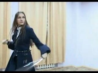 Девушка танцует казачий танец с шашками.