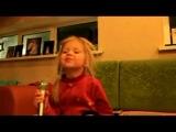 Маленькая девочка поёт песню, рюмка водки на столе...