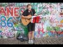 Крутой чувак поёт возле стены Джона Леннона в Праге