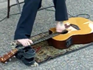 Музыкант-инвалид играет на гитаре пальцами ног.