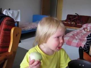 Маленькая девочка ест лук как яблоко