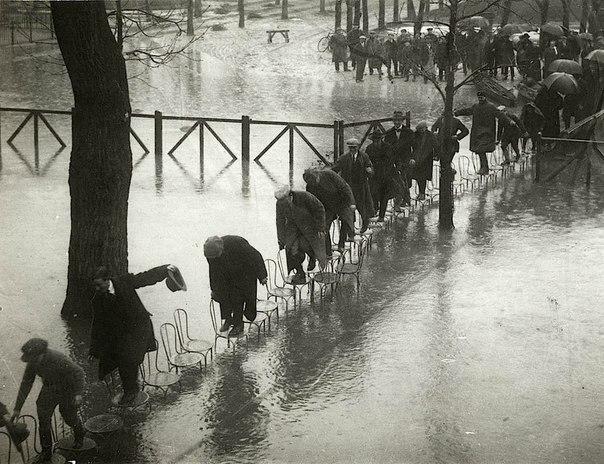 Люди идут по стульям на реке Мезон-Лаффитта, чтобы избежать наводнения реки Сены...