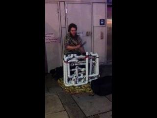 Уличный музыкант играет на странном самодельном инструменте