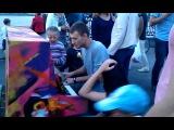 На дне города парень играет на уличном пианино