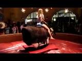 Горячая девушка танцует во время езды на механическом быке.