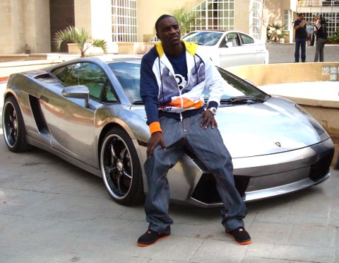 Akon sitting on his Lamborghini Gallardo