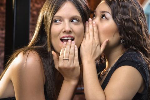 Привлекательная молодая женщина, шепотом секрет в другом ухе.