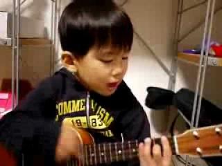 Очень маленький мальчик играет на гитаре.